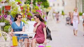 Two fashion shoppers woman with bags shopping on the street. Sale, consumerism and people concept. Caucasian girls enjoy stock video footage