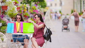 Two fashion shoppers woman with bags shopping on the street. Sale, consumerism and people concept. Caucasian girls enjoy. Two fashion colorful shoppers with bags stock video footage