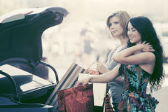 Two fashion women with shopping bags on car parking Stock Images