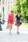 Two fashion women walking in the summer city. Two young women walking in the summer city Royalty Free Stock Image