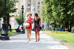 Two fashion women walking in the summer city Stock Photography