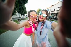 Two fashionable and beautiful best girlfriends in glasses, posing doing the general self, showing everyone its lifestyle royalty free stock photo