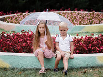 Two fashionable children under an umbrella in a summer park. Walk on a rainy day in a flowers garden. Copy space. stock photo