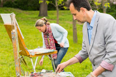 Two fashionable creative painters during an art class in a park. Two fashionable creative painters working  on a trestle and easel painting with oils and Royalty Free Stock Images