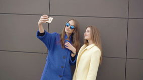 Two fashionable girls taking selfie in the coats 4K stock footage