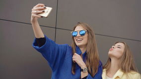 Two fashionable girls taking selfie in the coats and sunglasses 4K stock video footage