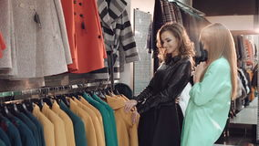 Two fashionable ladies choosing the coats in shop. In full HD stock video