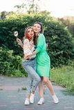 Two fashionable and positivity girls eating  sweet candies on stick. Two fashionable and positivity girls wearing in trendy clothes and professional makeup royalty free stock photo