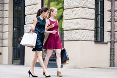 Two fashionable women carrying paper bags while shopping in summ Royalty Free Stock Photo
