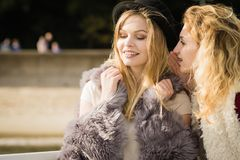 Two fashionable women gossiping. Two fashionable women wearing stylish outfits during warm autumnal weather gossiping together Stock Photo