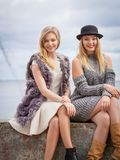 Two fashionable women outdoor. Two fashionable women wearing stylish outfits during warm autumnal weather spending their free time outdoor Stock Images