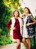 Two fashionable women outdoor. Two fashionable women wearing stylish outfits during warm autumnal weather spending their free time outdoor Stock Photography