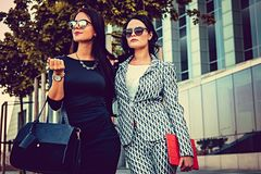 Portrait of two fashionable women on a street. Two fashionable women in stylish clothes and sunglasses posing in a middle of business urban district Stock Images