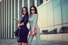 Portrait of two fashionable women on a street. Two fashionable women in stylish clothes and sunglasses posing in a middle of business urban district Stock Image