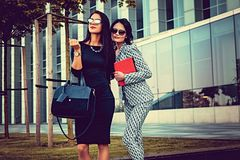 Portrait of two fashionable women on a street. Two fashionable women in stylish clothes and sunglasses posing in a middle of business urban district Stock Photography