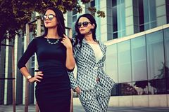 Portrait of two fashionable women on a street. Two fashionable women in stylish clothes and sunglasses posing in a middle of business urban district Royalty Free Stock Photography