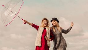 Two fashionable women and umbrella. Two fashionable women wearing stylish outfits holding transparent umbrella spending their free time outdoor Stock Photography