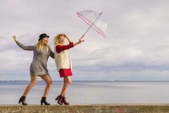 Two fashionable women and umbrella. Two fashionable women wearing stylish outfits holding transparent umbrella spending their free time outdoor Royalty Free Stock Photography
