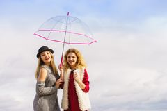 Two fashionable women and umbrella. Two fashionable women wearing stylish outfits holding transparent umbrella spending their free time outdoor Stock Photo