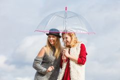 Two fashionable women and umbrella. Two fashionable women wearing stylish outfits holding transparent umbrella spending their free time outdoor Royalty Free Stock Photos