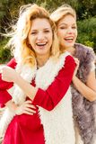 Two fashionable women outdoor. Two fashionable women wearing stylish outfits during warm autumnal weather spending their free time outdoor Royalty Free Stock Images