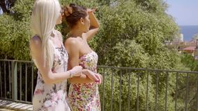 Two fashionable young woman out walking. Together arm in arm enjoying the summer sun stock video