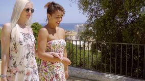 Two fashionable young woman out walking. Together arm in arm enjoying the summer sun stock footage