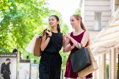 Two fashionable young women walking in the city during shopping Stock Photo