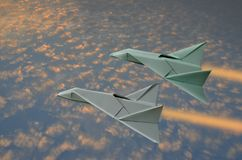 Two fast jet planes fly over golden clouds in early morning. Two fast jet planes fly over golden clouds in blue sky with morning sunlight royalty free stock photo