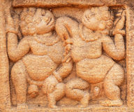 Two fat and happy people dancing on stone relief of 7th century temple in Badami town, India. Famous for rock cut architecture of Karnataka stock photography
