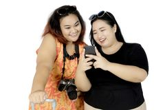 Two fat tourists using a smartphone on studio. Two fat tourists using a smartphone while standing in the studio, isolated on white background Stock Photo