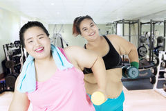 Two fat women with dumbbells in the gym Royalty Free Stock Images