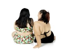 Two fat women sitting in the studio. Back view of two fat women wearing swimwear while sitting in the studio, isolated on white background Stock Image