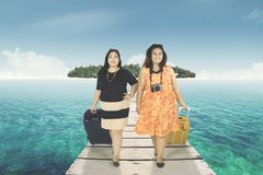 Two fat women walking on the jetty. Image of two fat women walking on the jetty while carrying luggage and looking at the camera Royalty Free Stock Image