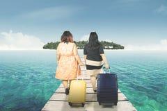 Two fat women walking toward an island. Two fat women carrying a suitcase while walking toward an island Stock Image