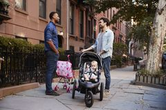 Two father friends with two kids talking in the street royalty free stock photo