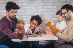 Two fathers play educational games with their children. Having fun Stock Photography