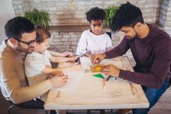 Two fathers play educational games with their children. Having fun royalty free stock images