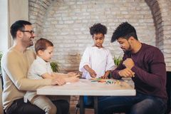Two fathers play educational games with their children. Having fun Royalty Free Stock Photo