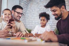 Two fathers play educational games with their children. Having fun Stock Images