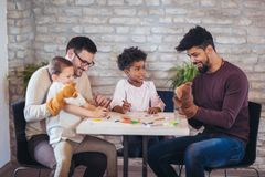 Two fathers play educational games with their children. Having fun stock image