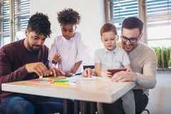 Two fathers play educational games with their children. Having fun Royalty Free Stock Photos