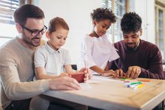 Two fathers play educational games with their children. Having fun Royalty Free Stock Photography