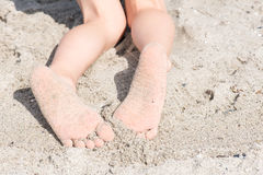 Two feet of a boy in sand at at beach Royalty Free Stock Photography