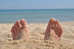 Two feet buried in sand Stock Image