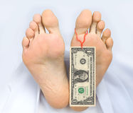 Two feet of dead body with banknote one dollar. Two feet of a dead body, with banknote one dollar attached to a toe. Covered with a white sheet Stock Image