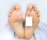 Two feet of a dead body, with blank sign. Two feet of a dead body, with an identification tag - blank sign  attached to a toe. Covered with a white sheet Royalty Free Stock Photo