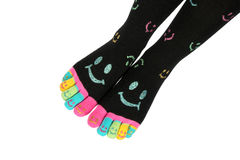 Two feet in happy socks with toes. Two feet in happy black socks with colorful smileys. The toes are colorful with smileys, too. Feet are arranged diagonal Royalty Free Stock Photography