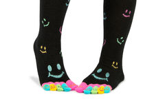 Two feet in happy socks with toes. Two feet in happy black socks with colorful smileys. The toes are colorful with smileys, too. The person is standing on the stock images