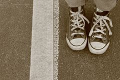 Two Feet and a Line. Converse on paved ground Stock Photos